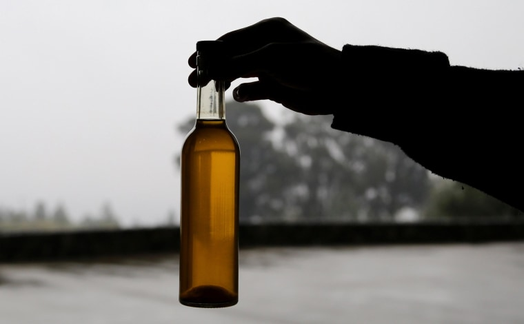 Image: A person holds a bottle of olive oil.