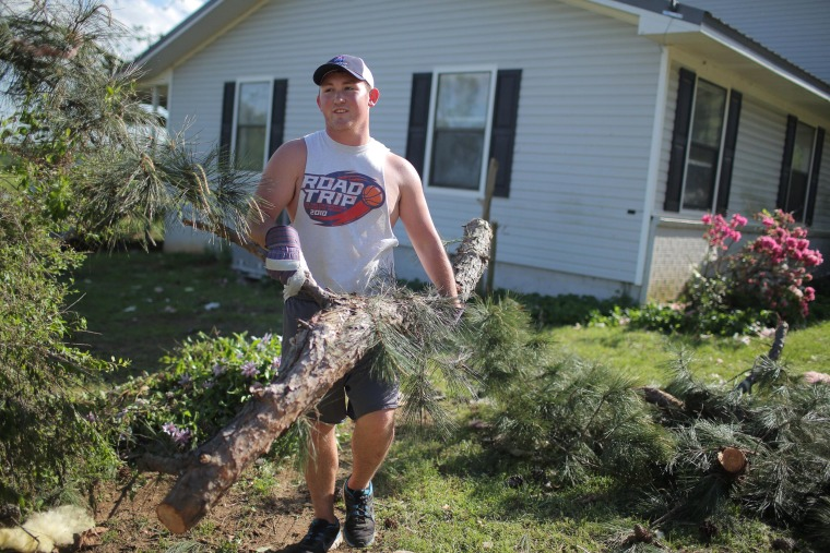 Image: Christian Gunter clears downed trees after a tornado in Vilonia, Ark.