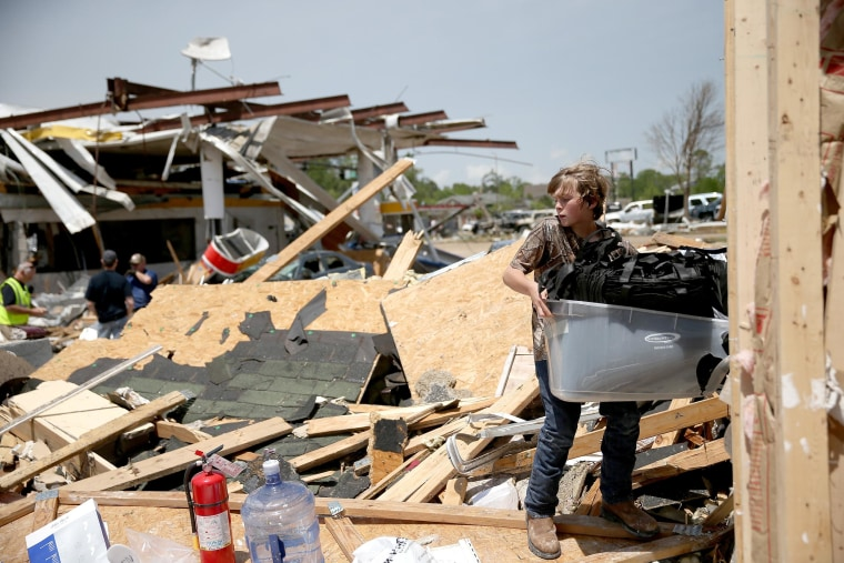 Image: Sam Smith helps a family friend salvage what he can from his business that was destroyed by a tornado on April 29, 2014 in Tupelo, Miss.