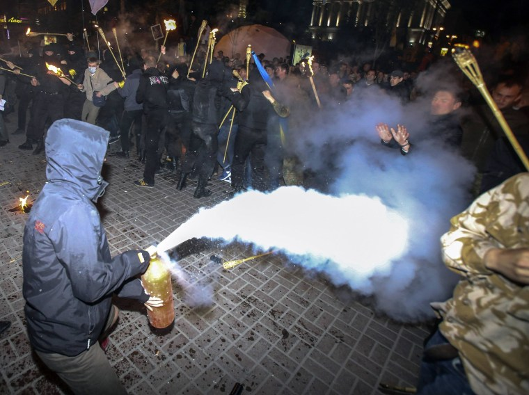 Image: A man uses a fire extinguisher as members of self-defence units of the Euromaidan movement attempt to prevent members and supporters of Ukrainian far-right radical groups from taking part in a torch-light procession in Kiev