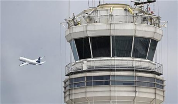 Image: A passenger jet flies past the FAA control tower at Washington's Ronald Reagan National Airport