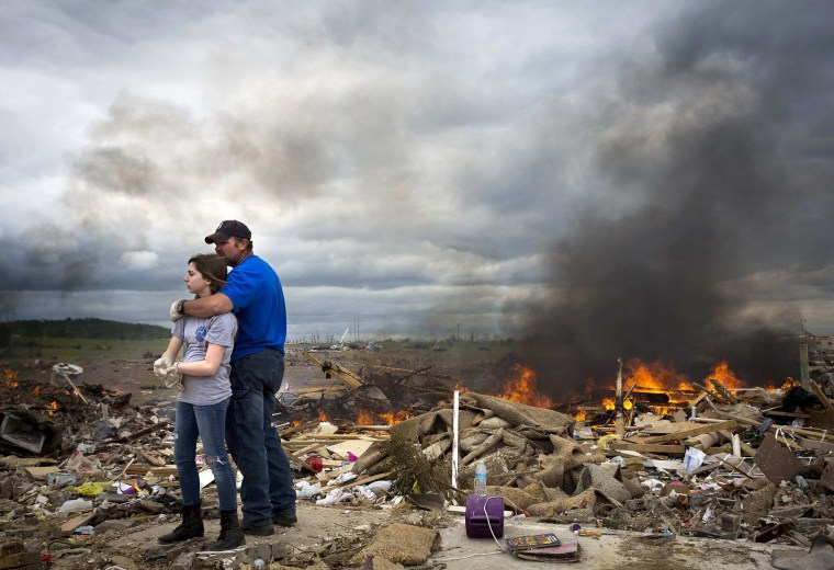Michael Stanek hugs his daughter Kennedy as they take a break from helping friends sift though the rubble of their homes in Vilonia, Ark. on April 30. Severe floods in Florida's Panhandle and coastal Alabama deluged roads and engulfed homes and cars on Wednesday, the latest mayhem created by a tornado-packing storm system that has killed at least 34 people in the United States this week.