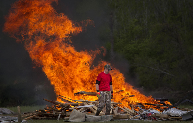 Image: Man walks away from a clean-up debris fire in Vilonia, Arkansas