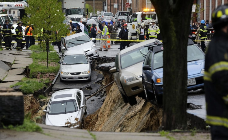 Image: Cars sit on the edge of a sinkhole in the Charles Village neighborhood of Baltimore