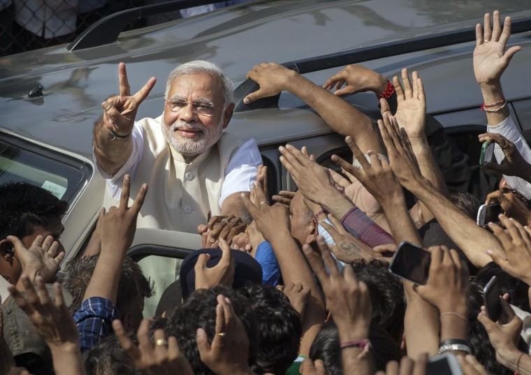 Image: BJP leader Narendra Modi shows his inked finger to supporters as he leaves a polling station