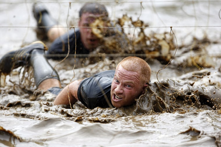 Image: Competitors swim through mud underneath electrified wires during a Tough Mudder in Vermont in 2012.
