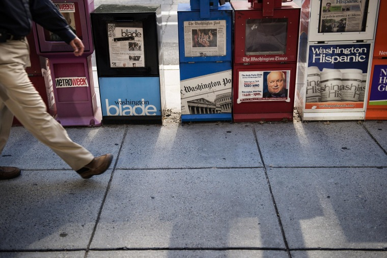 A man walks past a Washington Post newspaper box on Aug. 5, 2013 in Washington, D.C.