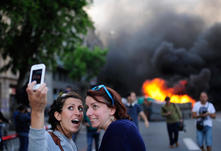 Tourists take a selfie as demonstrators burn a trash container during a May Day rally in Barcelona, Spain, on May 1, 2014.