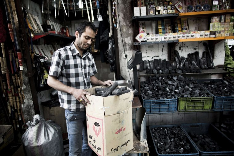 Image: Omid Kazemi poses next to his small coal shop