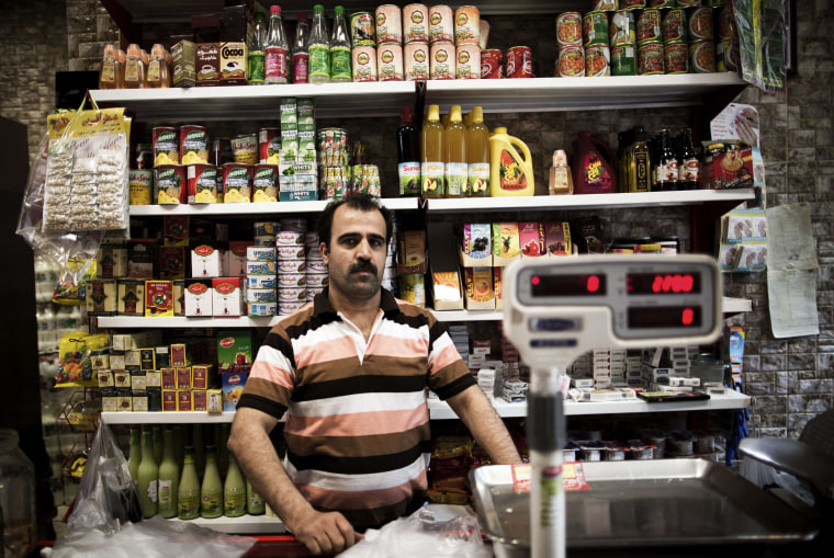 Image: Alireza Vafaei, 41, poses in his grocery in the Mokhtari neighborhood in southern Tehran