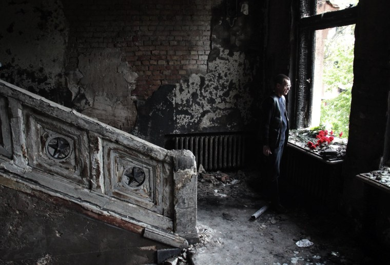 Image: A man lays flowers inside the burnt trade union building in Odessa