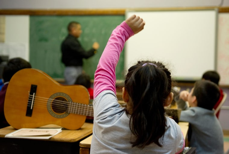 A student raises her hand to ask a question during a class.