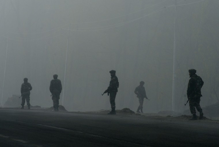 Image: Indian army soldiers patrol along a roadside amongst heavy fog outside a polling station