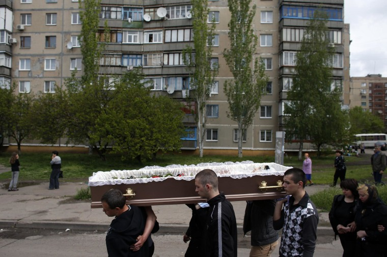 Image: Relatives carry coffin of 21-year-old nurse Izotova at her funeral in Kramatorsk, eastern Ukraine