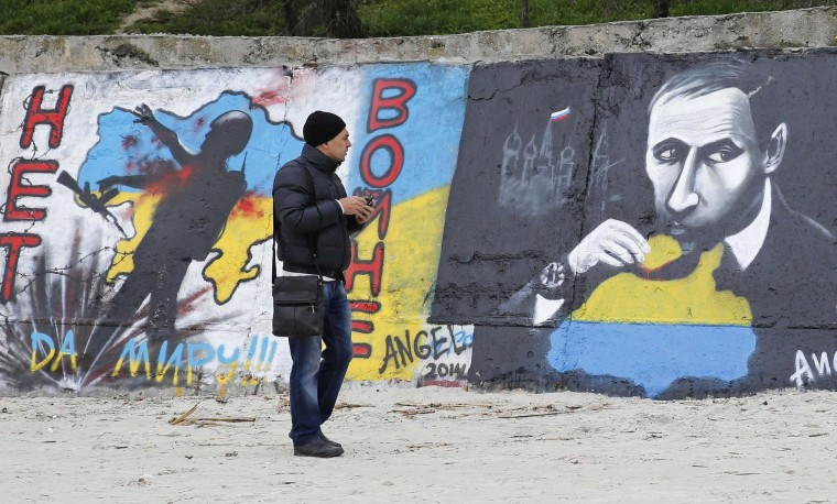 Image: A man looks at a graffiti produced to support the territorial integrity of Ukraine and to protest Russia's annexation of Crimea in Odessa
