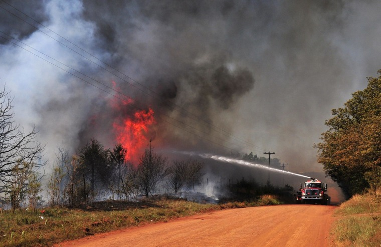 Image: Firefighters work to extinguish a flare up in Guthrie, Okla