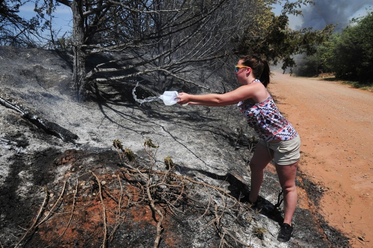 "Myka Burton pours water on a roadside hot spot on Monday, May 5, 2014, in Guthrie, Okla. ""I'm doing anything I can to help"" said Burton. Firefighters worked Monday to battle a large wildfire in central Oklahoma that destroyed at least six homes and left at least one person dead after a controlled burn spread out of control."