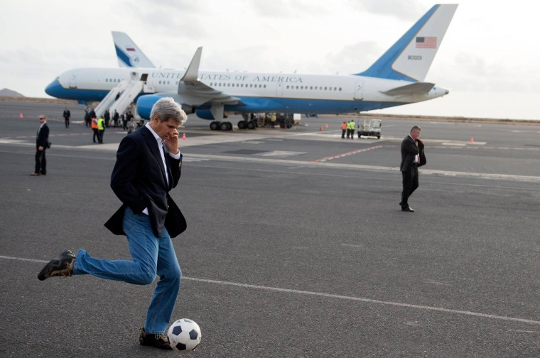 U.S. Secretary of State John Kerry kicks a soccer ball around during an airplane refueling stop at Sal Island, Cape Verde, on May 5, 2014.