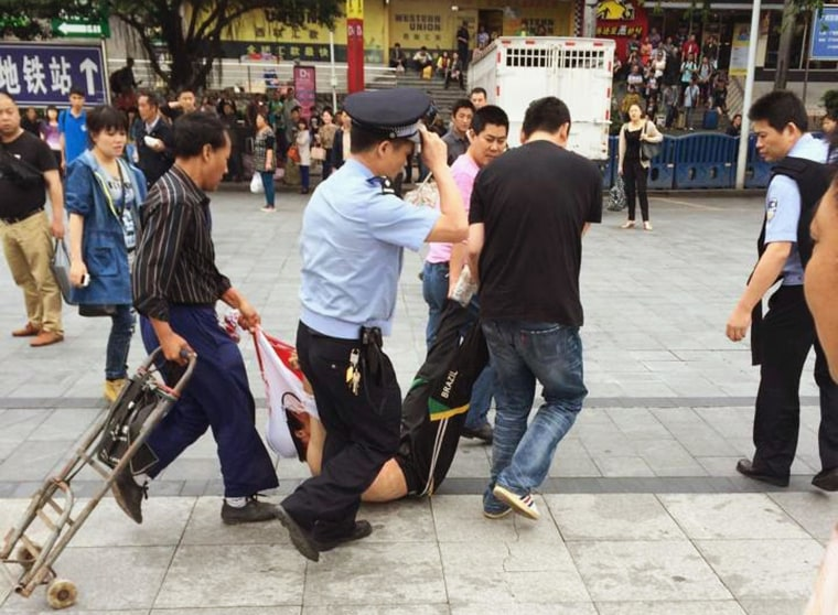 A man, whom local media say is a suspect, is detained after a knife attack at a railway station in Guangzhou, Guangdong province May 6.