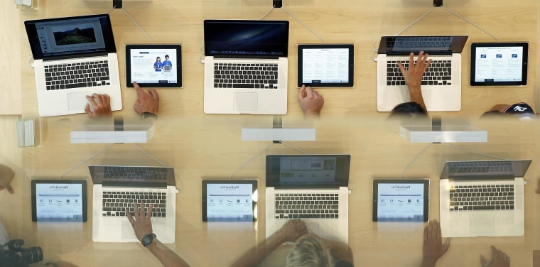 Customers look at MacBook Pros, during the official opening of the largest Apple shop in southern Europe, at Passeig de Gracia in Barcelona, July 28, 2012. The bottom image is a reflection on a glass surface.