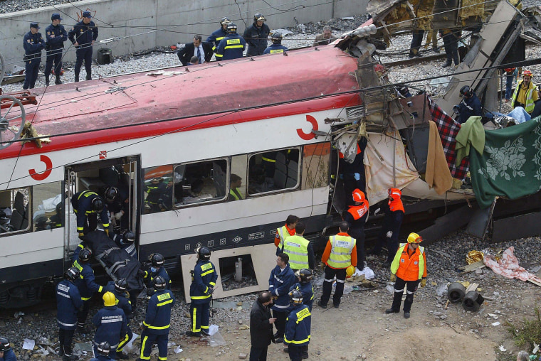 Image: Rescue workers evacuating the body of a victim after a train exploded at the Atocha train station in Madrid
