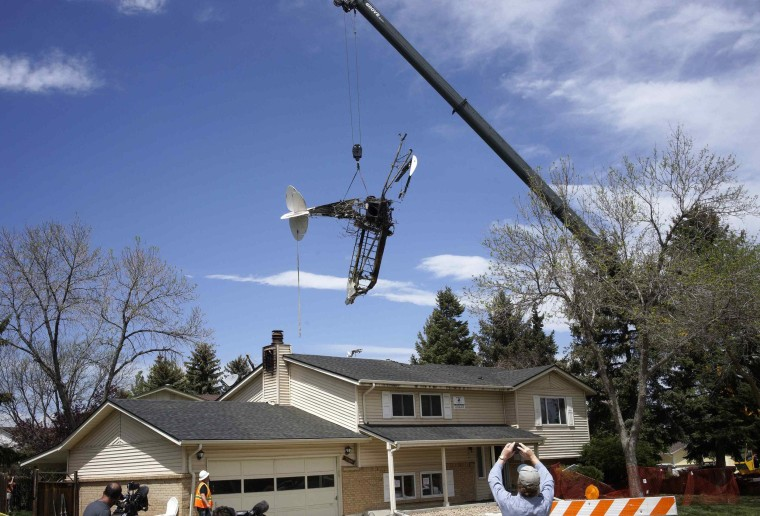 Image: Wreckage of a small plane that crashed into a house is lifted by a crane in Northglenn