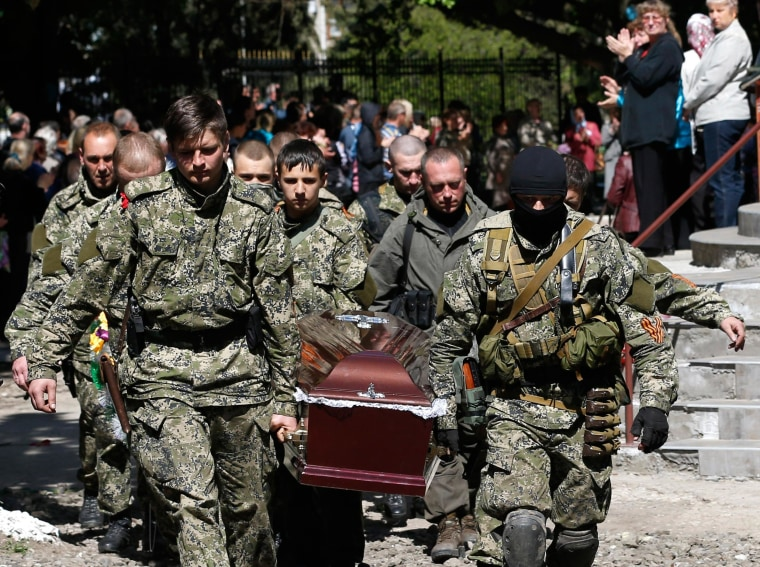 Image: Pro-Russian gunmen carry the coffin of a person killed in Slovyansk