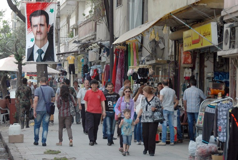 Image: People walk past a placard bearing a portrait of President Bashar al-Assad on May 7, 2014 in a government-controlled district of Homs.