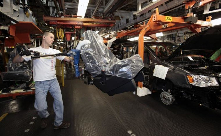 A Chrysler auto worker load the seats into Chrysler minivans during the production launch of the new 2011 Dodge and Chrysler minivans at the Windsor Assembly Plant