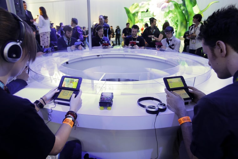Image: Attendees play video games on the Nintendo 3DS at the Nintendo Wii U software showcase during the E3 game show in Los Angeles