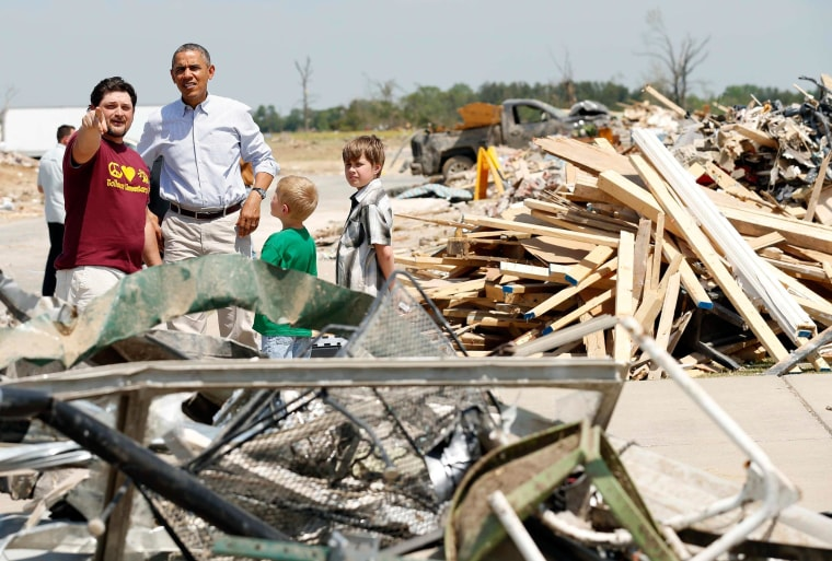 President Barack Obama talks with Daniel Smith and sons Gabriel Dority (R) and Garrison Dority as he visits the tornado devastated town of Vilonia, Arkansas May 7, 2014.
