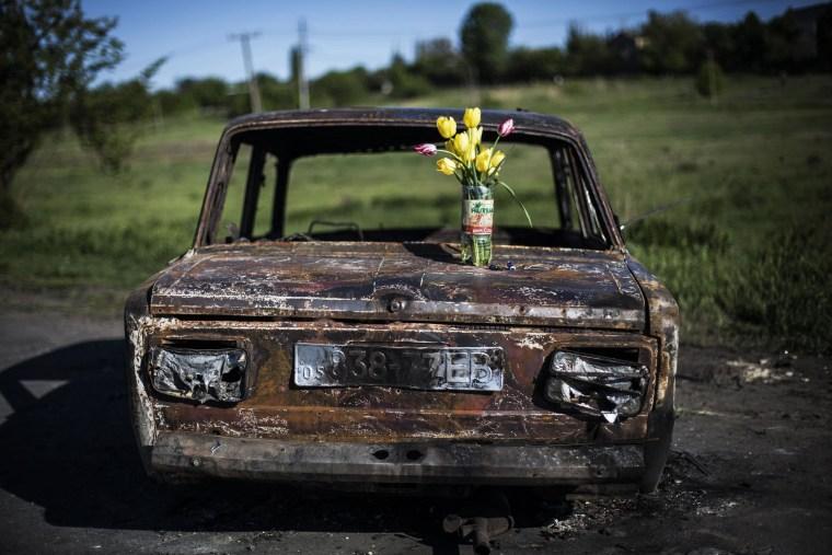 Image: Bouquet of flowers atop shell of car near Slovyansk, Ul