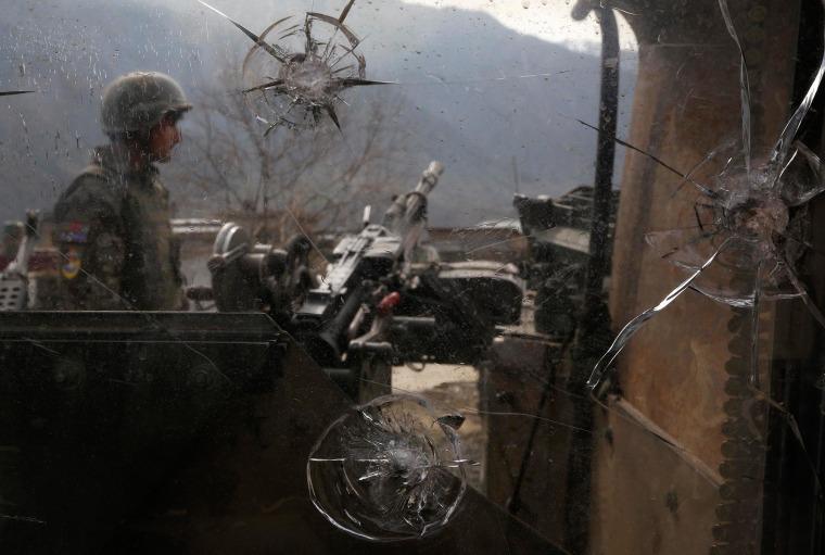 Image: An Afghan National Army soldier is seen through damaged glass at an outpost in Kunar province