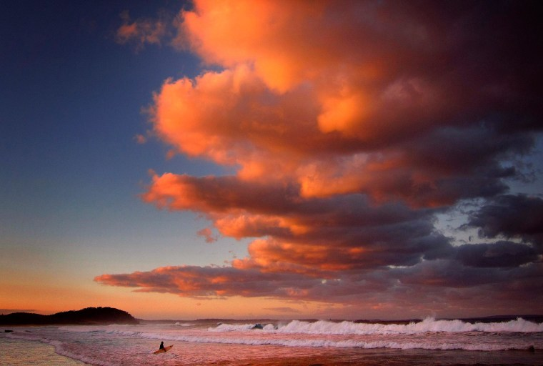Image: Surfer holding her board wades through the surf as clouds above are lit by the setting sun at Mollymook Beach on the south coast of New South Wales