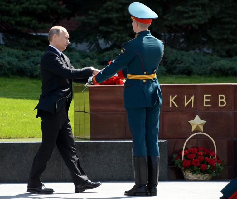 Image: Russia's President Vladimir Putin lays flowers at a polished stone block bearing the inscription Kiev, one of several honoring cities of the former Soviet Union