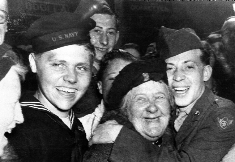 An American soldier, right, hugs an Englishwoman as other U.S. soldiers celebrate the surrender of Germany on May 7, 1945, in London's Piccadilly Circus.