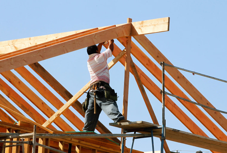 Image: A construction worker works on the framework for a single family home under construction in Los Angeles