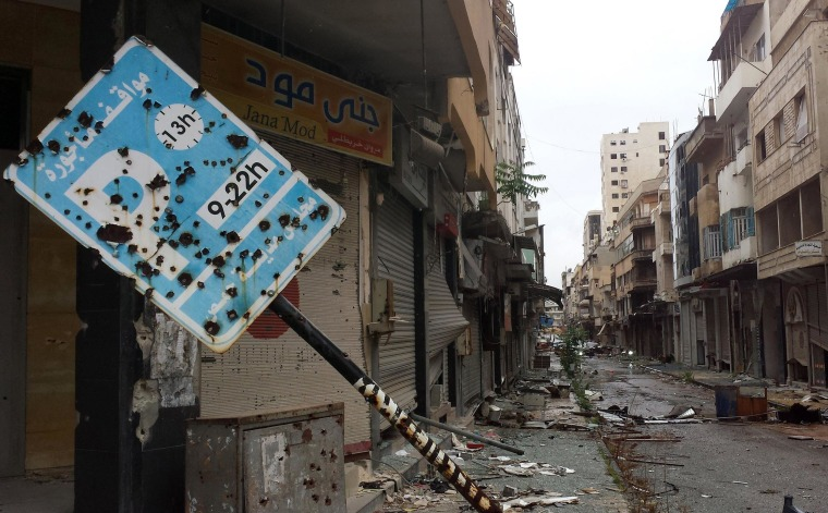 A bullet-riddled parking sign stands amid debris in a deserted street leading into the city of Homs, Syria on May 8, as rebel fighters withdrew from the city center.