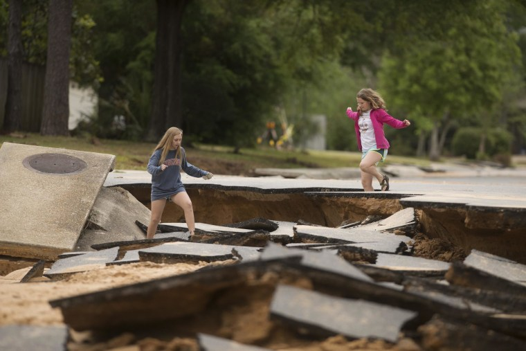 Image: Residents survey the damaged road in their Cordova Park neighborhood in Pensacola