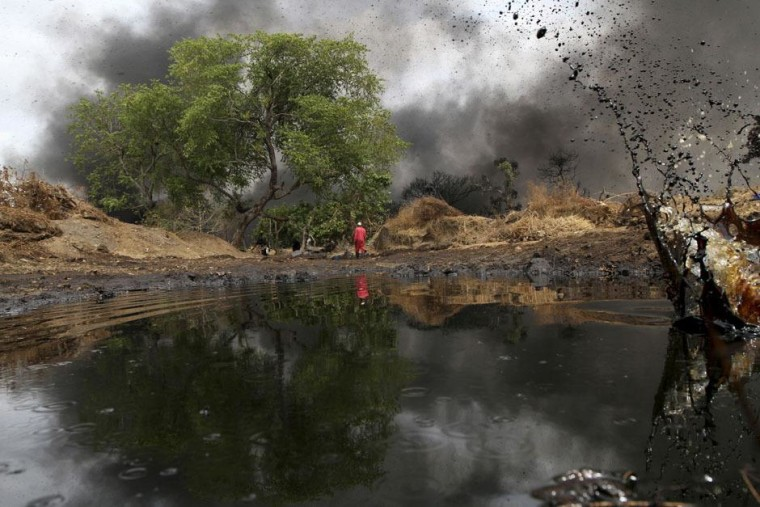 Image: A man walks as crude oil spills from a  pipeline in Dadabili, Niger state