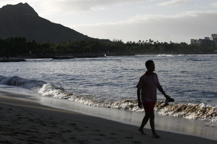 Image: A man is silhouetted as he walks along Waikiki Beach February 27, 2010 in Honolulu, Hawaii
