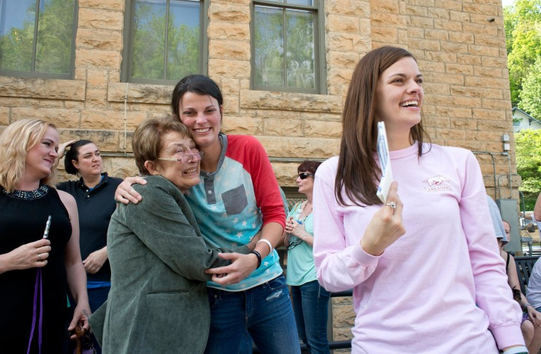 Image: Jennifer Rambo, right, smiles as her partner Kristin Seaton, center, hugs Sheryl Maples, left, the lead attorney who filed the Wright v. the State of Arkansas lawsuit