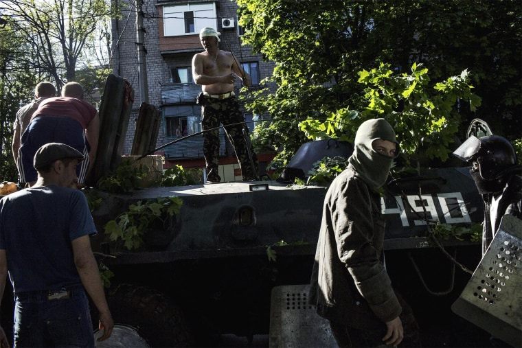 Pro-Russian activists guard a Ukrainian tank on May 10 in Mariupol, southeastern Ukraine. The tank was left by the Ukrainian army the day before due to a faulty engine as fighting between Ukrainian troops and pro-Moscow militants erupted. Witnesses in Mariupol told AFP the fighting was ferocious and involved an exchange of automatic gunfire and shelling from eight armoured vehicles. A day later after the clashes, several blocks in the centre of this normally placid port city of some 500,000 resemble a post-apocalyptic wasteland with the police completely absent and young men building makeshift barricades around gutted, blackened buildings.