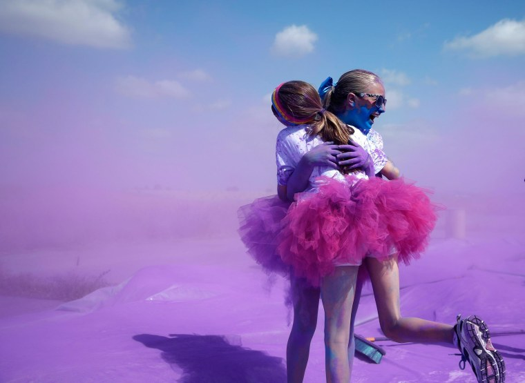Image: Competitors hug after running through colored powder at the Orange County Color 5K Run in Irvine, California