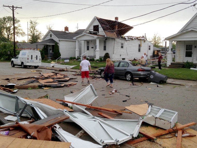 Image: People walk through debris after a storm in Evansville, Ind.
