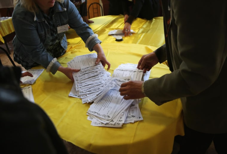 "Image: Election officials sort through a pile of ""yes"" votes for independence for eastern Ukraine"