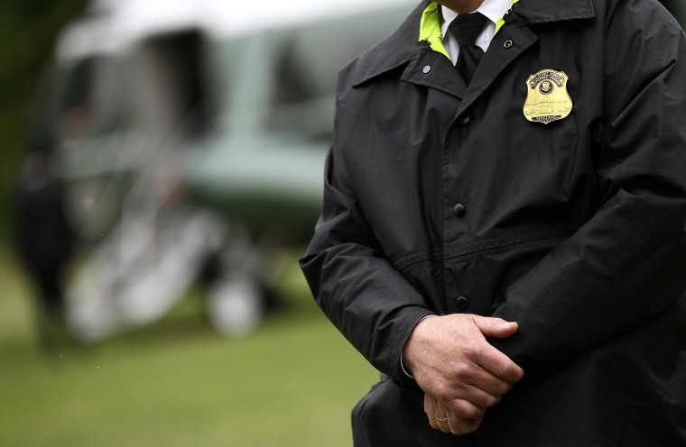 A member of the U.S. Secret Service Uniformed Division stands his post as U.S. President Barack Obama departs the White House in 2012 in Washington.