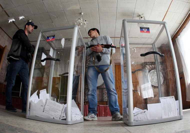 Image: An armed pro-Russian activist stands guard near ballot boxes in Donetsk, Ukraine