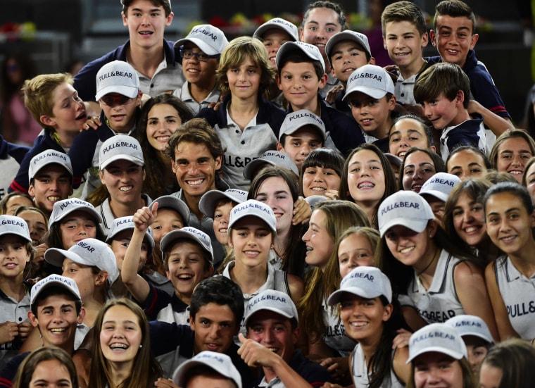 Image: Spanish player Rafael Nadal poses with children