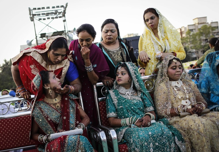 Image: A Muslim bride speaks to her relative as they wait for start of mass marriage ceremony in Mumbai